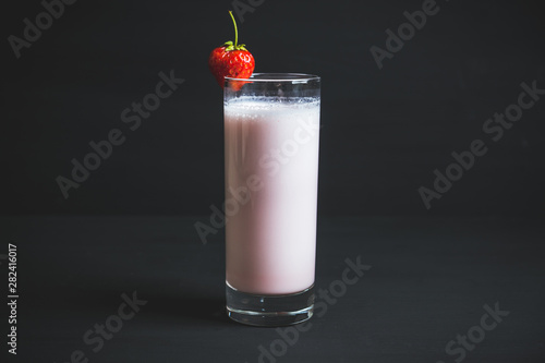 Strawberry milkshake with on the rustic background. Selective focus.