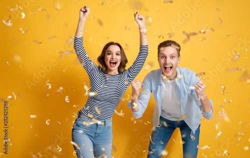 joyful couple on yellow background Fototapet