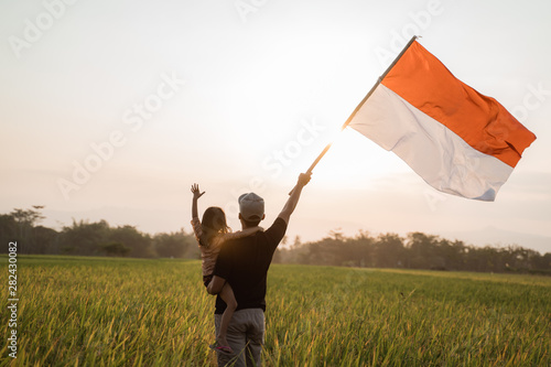 Poster Individuel father carrying little girl pride flapping Indonesian flag with happiness in the rice field