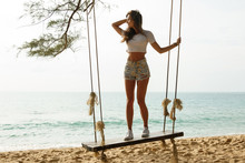 Woman Wearing Jeans Shorts Relax On The Swing  On The Beach