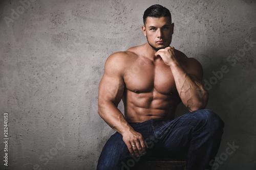 Cuadros en Lienzo Massive bodybuilder posing beside the concrete wall