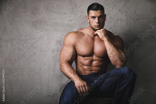 Fotografie, Obraz Massive bodybuilder posing beside the concrete wall