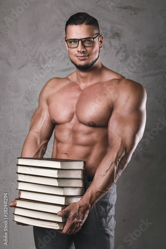 Smart and muscular man with a heap of books