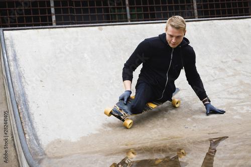 Motivated handicapped  guy with a longboard in the skatepark Obraz na płótnie