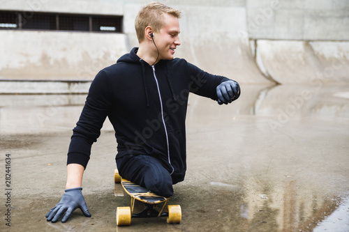 Motivated handicapped  guy with a longboard in the skatepark Fototapete