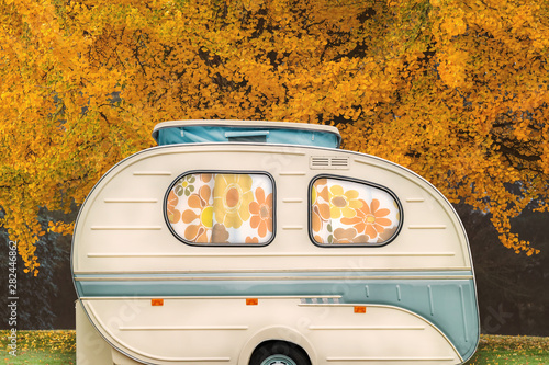 Canvas Prints Countryside Vintage seventies white caravan with flower curtains in front of