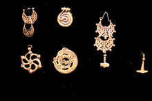Retro Amulets Of Yellow Metal, Close-up. Bronze Pendants With Runes And Animals On A Black Background.