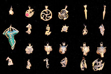 Metal Pendants, Close-up. Vintage Amulets Of Gold With Runes And In The Form Of Animals On A Black Background.
