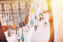 Pendants With Colored Stones Hang On The Ropes. Amulets With Beautiful Decorations In The Sun.