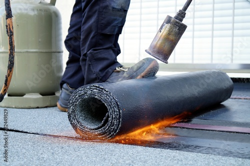 Photo Flat roof installation with propane blowtorch during construction works with roofing felt