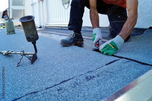 Fotografía  worker installing tar foil on the rooftop of building