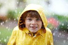 Beautiful Little Kid Boy On Way To School Walking During Sleet, Heavy Rain And Snow With An Umbrella On Cold Day. Happy And Joyful Child In Colorful Yellow Coat Fashion Casual Clothes