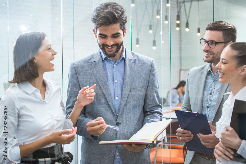 Fototapeta Business team discussing business documents, standing in the office lobby