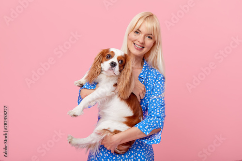 Portrait of smiling young blond woman in summer hat embracing king Charles spaniel dog. owner and pet relations concept. Veterinary health. Isolated front view on pink background. - 282458227