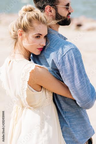 Obraz na plátne young blonde woman hugging bearded boyfriend at beach