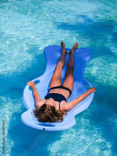 Beautiful athletic sun tanned girl floating on a pool float ...