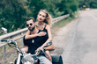 young couple of bikers embracing on black motorcycle on road near green forest