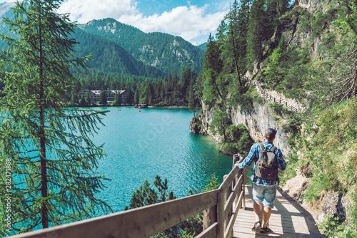 man walking by hiking trail around braies lake in italy dolomites mountains Fototapet