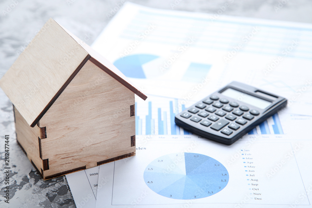 Fototapeta Wooden house model with financial papers and calculator