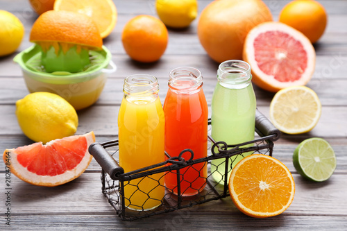 Photo Stands Juice Citrus juice in glass bottles with fruits on wooden table