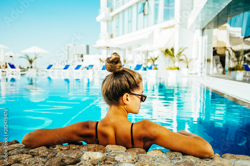 Obraz Woman relaxing by the pool at luxury hotel on the island - fototapety do salonu