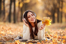 Beautiful Woman With Headphones And Maple Leafs Lying On The Ground In Autumn Park