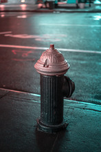 A Water Hydrant Painted Black And Purple In The Street At Night