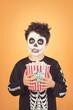Leinwanddruck Bild Happy Halloween.funny child in a skeleton costume with popcorn