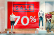 canvas print picture - Seasonal discounts in the store. Big red banner with text SALE 70 percent on a shop windows and mannequins dressed in casual clothes. Black friday in store, discount shop