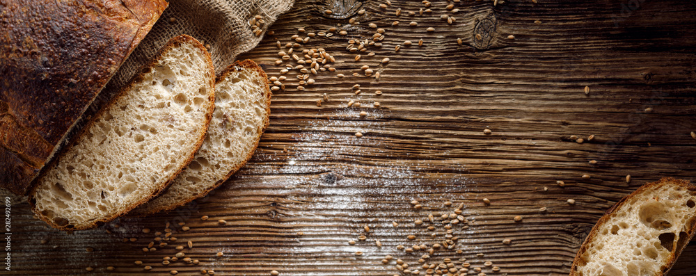 Fototapeta Bread,  traditional sourdough bread cut into slices on a rustic wooden background, close-up, top view, copy space. Concept of traditional leavened bread baking methods