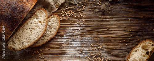 Photo Stands Bread Bread, traditional sourdough bread cut into slices on a rustic wooden background, close-up, top view, copy space. Concept of traditional leavened bread baking methods