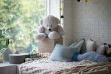 Cozy Children's Room In Bright Soft Colors, Pillows And A Blanket Are Lying On The Bed