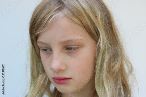 Portrait of a blonde adolescent girl looking down and away Wallpaper Mural