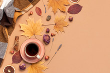 Autumn Flat Lay Composition. Cup Of Tea, Checkered Plaid, Autumn Dry Leaves, Roses Flowers, Orange Circle Cones Decorative Pomegranate Cinnamon Sticks On Brown Beige Background Top View. Fall Concept