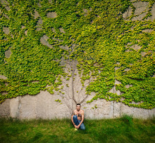 Portrait Man With Tattooed Chest Sitting At Wall Overgrown With Ivy