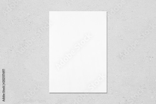 Fototapeta Empty white vertical rectangle poster mockup with soft shadow on neutral light grey concrete wall background. Flat lay, top view obraz