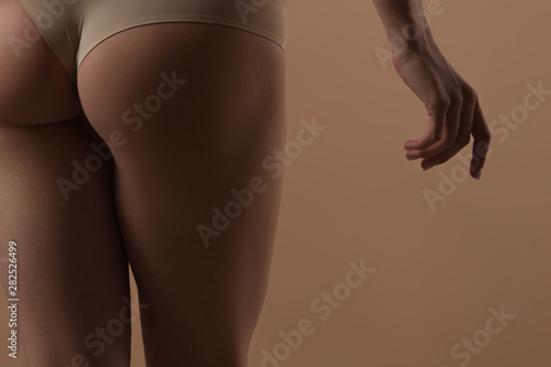 Fotografia Thin young woman in underwear on beige background