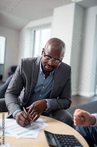 Dark-skinned man signing documents sitting near tax lawyer - 282528863