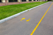 An Asphalt Road With Yellow Markings And Directional Arrows, A Roadside With A Green Lawn And A Stone Fence.