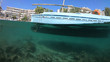 Underwater split photo of beautiful traditional fishing boat in small port of Greek Aegean island