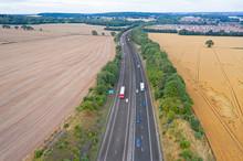 Aerial View Over Motorway Across Ripe Grain Fields In UK