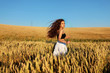 The pretty girl with long hair in stylish white pants and black top running in rye .Stylish girl.Long haired,curly girl.Girl in rye.Summer photos of  in the field. Dynamic photo.Sunset light.