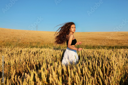 The pretty girl with long hair in stylish white pants and black top running in rye .Stylish girl.Long haired,curly girl.Girl in rye.Summer photos of  in the field. Dynamic photo.Sunset light. - 282538224