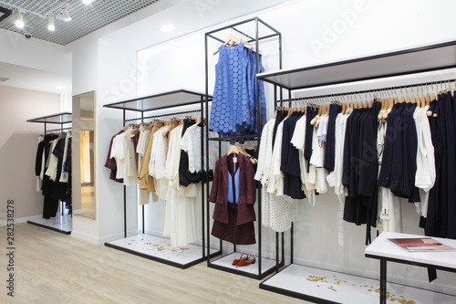 Obraz Interior of clothing store .Bright interior.Minimalistic style.Clothes hang on hanger.Trendy colors - fototapety do salonu