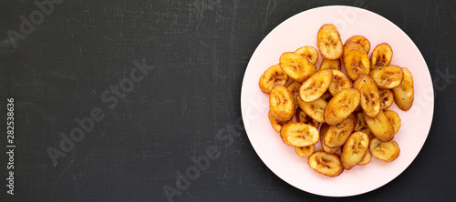 Fototapeta Homemade fried plantains on a pink plate on a black surface, overhead view. Flat lay, from above, top view. Space for text. obraz
