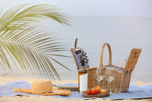 Wicker Picnic Basket With Food And Wine On Blanket Near Sea