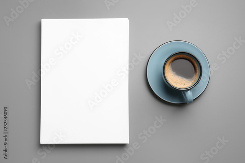 Fototapeta Blank paper sheets for brochure and cup of coffee on grey background, flat lay. Mock up obraz