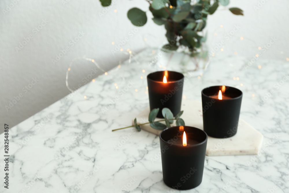 Fototapety, obrazy: Burning candles and green branches with fairy lights on marble table