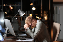 Tired Young Businessman Working In Office Alone At Night