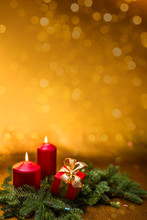 Gifts With Bows, Burning Red Candles And Spruce Branch On A Golden Background.